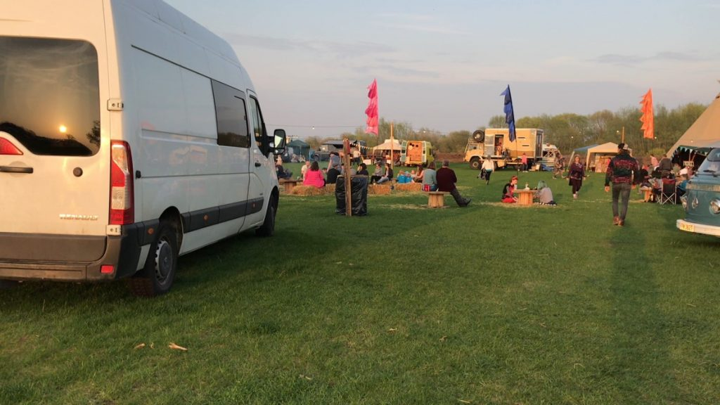 White van parked facing the camp quirky festival close by