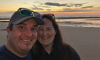 Darren and Rebecca on a beach with sunset behind
