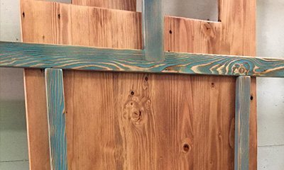 Pine showing the grain of wood with a light stain in teal